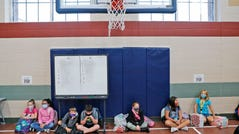 Wearing masks to prevent the spread of COVID19, elementary school students wait in the gym before school starts for the day in Godley, Texas, Wednesday, Aug. 5, 2020. Three rural school districts in Johnson County were among the first in Texas to head back to school for in person classes for students.