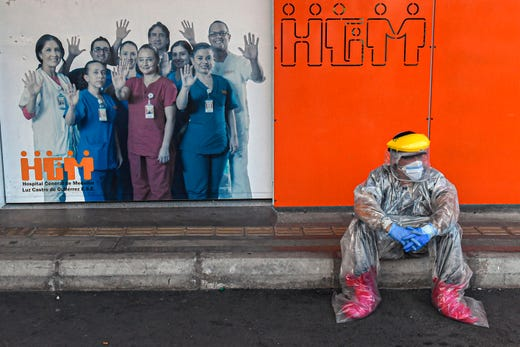 A health worker takes a break outside of Medellin's General Hospital, amid the COVID-19 pandemic, in Medellin, Colombia on Aug. 3, 2020.