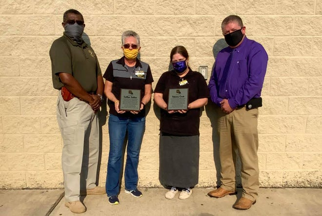 Sheriff Mark Herford honoring Sallye Salter, Tiffany Cook, and Ashley Darbonne (not pictured) in Ragley for their part in the apprehension of Neil P. Broussard. Pictured are Chief of Detectives Sylvester Denmond, Sallye Salter, Tiffany Cook, and Sheriff Mark Herford.