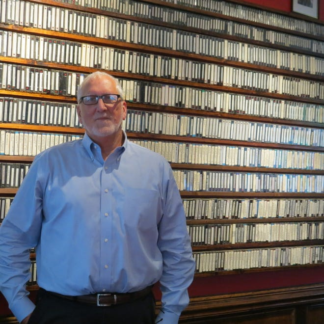Greg Stockton stands in front of 30 years worth of infrared videos he has made at airports, military bases, hospitals, schools and more across the country.
