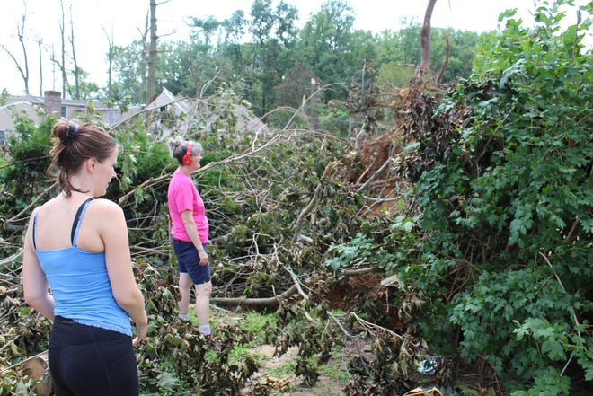 Pam Willis and her niece Valerie Pounders look at debris covering her backyard after Tropical Storm Isaias Aug. 6. The storm damaged much of Willis' neighborhood near Moore's Lake.
