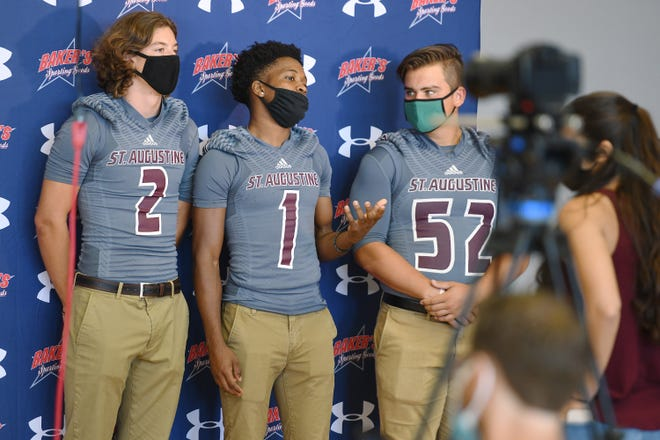 St. Augustine quarterback Sammy Edwards (2), cornerback Dequan Stanley (1) and lineman Joe Hiers wear their protective masks as they prepare to be interviewed during Thursday's Media Day for area high school football teams. [Bob Self/Florida Times-Union]