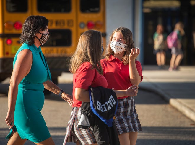 Sophia Nicholas, Mary Nicholas and Rebecca Juliano, left, emerging leaders teacher, walk back to class after a media interview during the first day back to school at McKeel Academy in Lakeland on Thursday. [ERNST PETERS/THE LEDGER]