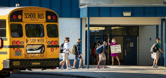 Students wearing masks walk to class after arriving on school buses during the first day back to school at McKeel Academy in Lakeland on Aug. 6. ERNST PETERS/THE LEDGER