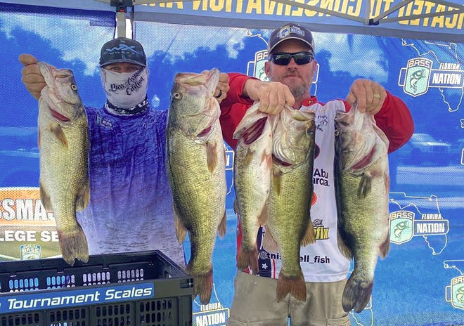 Matt Keeble, right, of Lakeland Bassmasters, placed first in the Co-Angler division with 25.90 pounds and a big bass of 8.09 pounds during the Florida Bass Nation Central Region Pro-Am Qualifier on the Harris Chain July 25. At left is Weighmaster Glenn Cale. Keeble is currently in the lead in the Co-Angler standings heading into the last event of the season on the Kissimmee Chain on Aug. 23.