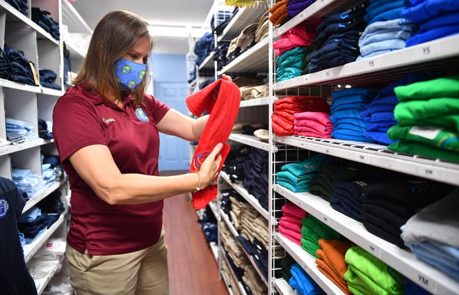 Cynthia Holliday, co-owner of Children's World Uniform Supply on Bee Ridge Road, folds shirts Thursday in hopes of a busy weekend. Florida's 2020 back-to-school sales tax holiday runs Friday through Sunday. [Sarasota Herald-Tribune / Mike Lang]