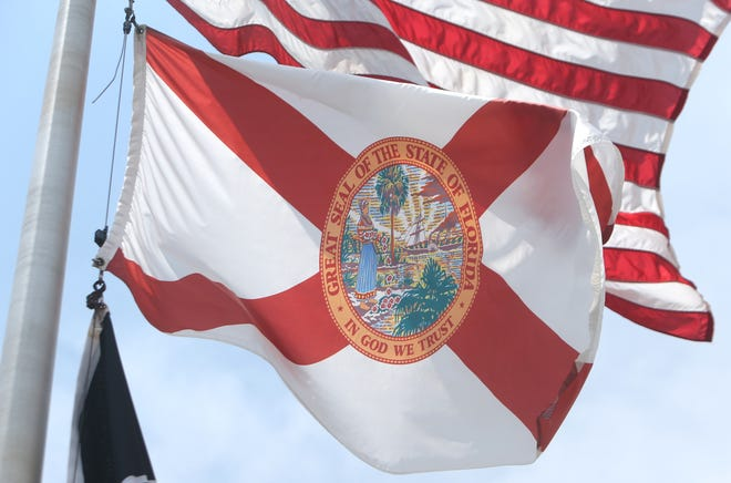 "The Florida State Flag flies over the Bay County Government Center on Monday. The Florida state motto ""In God We Trust"" is displayed on the Florida State Flag.  [PATTI BLAKE/THE NEWS HERALD]"