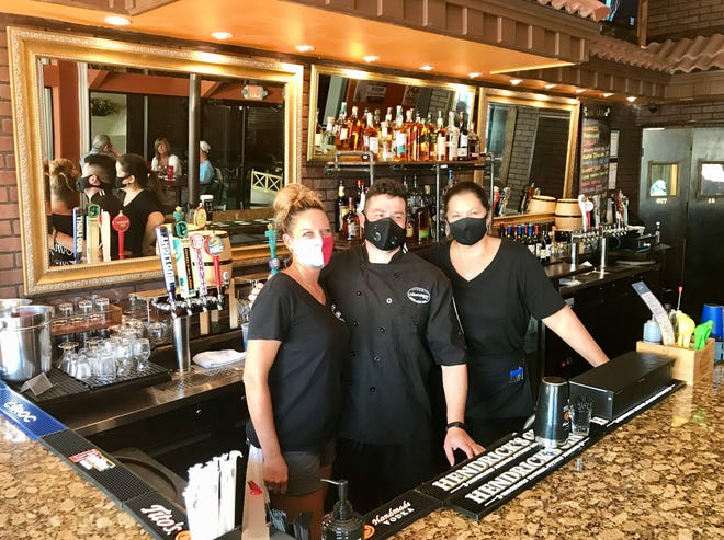 (Left to right) Server-bartender Terisa Korth, chef Raph Arca and server-bartender Donna Barnes stand inside Pub Americana in downtown Melbourne.