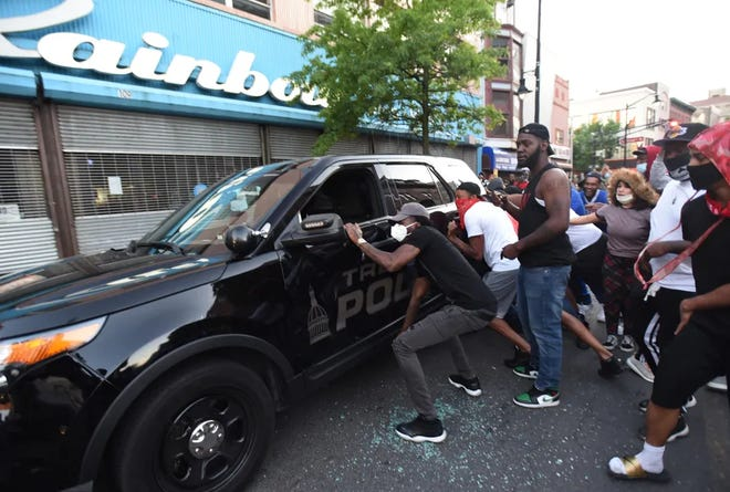 Protesters try to turn over a police SUV in Trenton on the evening of May 31.