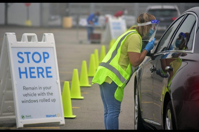 Chippewa Walmart employee Darla Miller of East Palestine, Ohio, goes to the window of a patients car and registers them for COVID-19 virus testing.