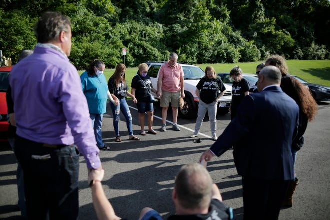 Family members and survivors join hands for a prayer before heading to a Southgate city council meeting at the former site of the Beverly Hills Supper Club in Southgate, Ky., on Wednesday, Aug. 5, 2020.