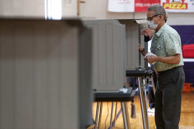 Marlon Crow sets up a voting booth for a resident to use at Clarksville High School in Clarksville, Tenn., on Thursday, Aug. 6, 2020.
