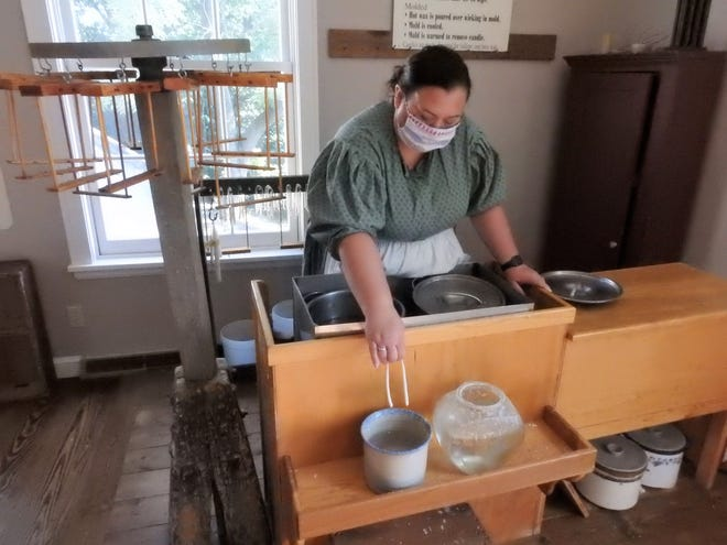 Interpreter Amy Trejo demonstrates candle making at the Hay Craft and Learning Center in Roscoe Village. The recreation of a canal era town has remained a major bright spot of local tourism during the pandemic.