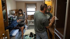 """Lake Superior State University junior Rebecca Weipert of Leroy and her father William Weipert disinfect room in Osborn Hall during a move-in day for students at Lake Superior State University in Sault Ste. Marie in Michigan's Upper Peninsula on Wednesday, August 5, 2020. """"It's stressful to send them into to something you don't know if it's truly safe or not. We know it's not 100 percent safe,"""" Weipert said about his daughter returning to campus. """"We're excited for her to get to her halfway point but we're equally as nervous about her having to do it this way."""" This year Weipert brought extra masks and supplies for her own room. She has one of her five classes online due to the class size. """"A lot of students are saying they think that it's going to go back online because people aren't going to follow the rules. I really hope it doesn't happen. It's hard to learn online especially with certain classes. That's why we're here is to learn and get the full potential of every class to get that kind of education,"""" she said."""