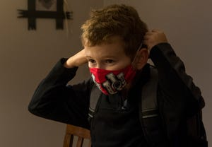 Ethan Fehrenbacher, 11, puts on his Indiana University mask as he prepares to leave for the first day of school Thursday morning, Aug. 6, 2020. Fehrenbacher is entering fifth grade at Good Shepherd School.