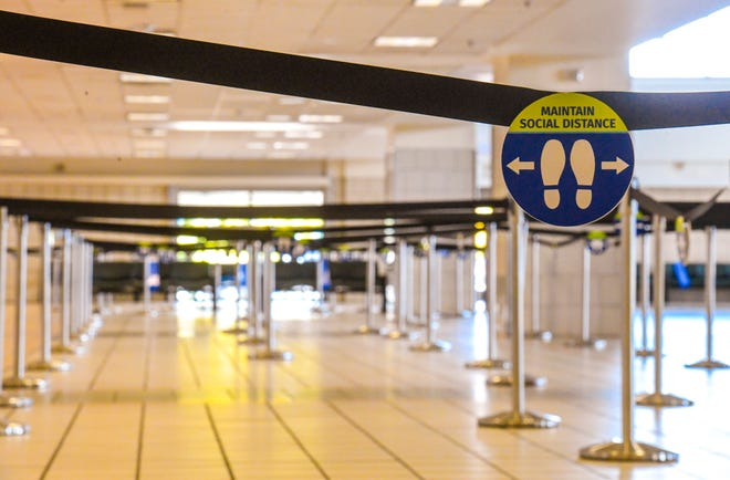 One of the many signs that hangs from stanchion straps in an empty ticket sales lobby, serve as a reminder of social distancing to travellers, during a midday visit to the A.B. Won Pat International Airport in Tamuning in this Aug. 6 file photo.