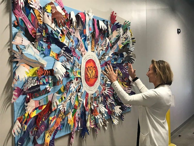 Shellie Gorman, principal at The Richland School of Academic Arts, 1456 Park Avenue West, admires artwork done by students of their hands on a wall inside the school. Lou Whitmire/News Journal