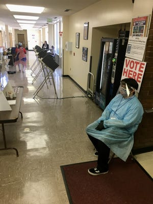 Election worker Kieran Bowien (right, foreground) waits during a slow moment during voting on August 6, 2020 at the Shelby County Board of Education. Bowien is 18 years old and said this is the first time he's worked in an election. His title is machine operator. He said the election commission provided the protective equipment, including the gown, gloves and face shield.