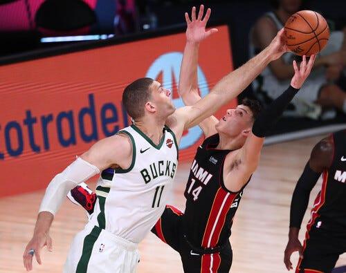 Bucks center Brook Lopez knocks the ball away from Heat guard Tyler Herro in the first half on Thursday.