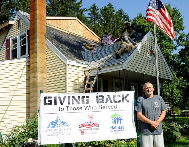 United States Marine Corps veteran Jason Bunn stands in front of his Newark home as workers replace the roof on Thursday, Aug. 6, 2020. Through a partnership between Lifetime Quality Roofing and Storm Restoration, Owens Corning's National Roof Deployment Project, Habitat for Humanity Mid-Ohio, and Haus Builders Bunn was able to get needed home repairs including a free roof and discounted gutters.