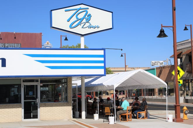 Customers in outdoor seating at TJs Diner at 119 E. Main St., in Farmington, on Aug. 6, are being served food. TJs and three restaurants are seeking to have the food service permits reinstated after violating the state's public health orders.