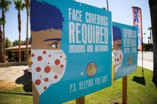 A sign stating face masks are required during the COVID-19 pandemic sits on the corner of Sunrise Way and Tahquitz Canyon Way on Thursday, August 6, 2020, in Palm Springs, Calif.