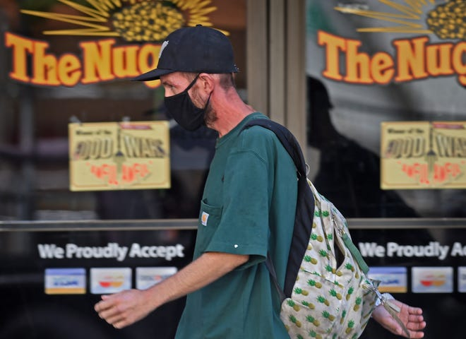 A man wears his mask as he walks in downtown Reno on August 5, 2020.