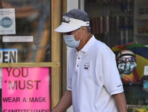 A man wearing his mask walks past of the Luck 7 Gifts store in downtown Reno on August 5, 2020.