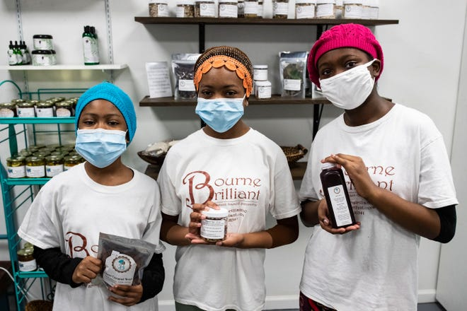 Sisters Nadira, 9, left, Zaira, 12, and Lyrica, 13 pose for a photo with products from their company Bourne Brilliant, where the three girls and their mom make mainly vegan products. The idea started out as a way to raise money for charity and led to the girls opening a shop in Railroad Square.