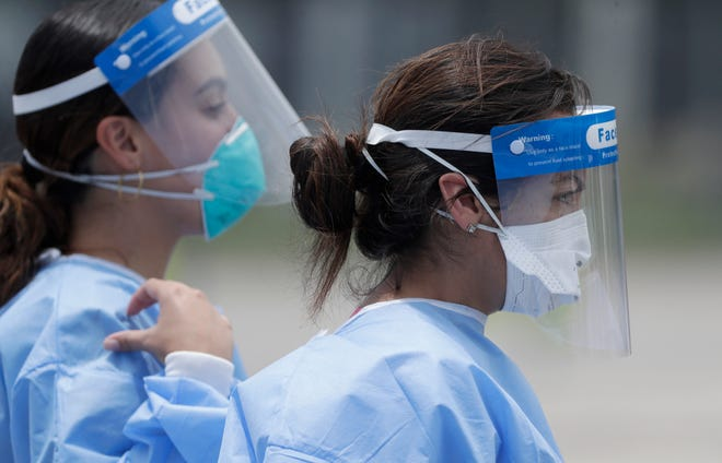 Health care workers at a COVID-19 test site in Miami Gardens in August.