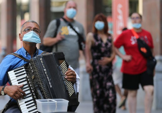 An accordion player wears a protective facemask as he plays on a street in Antwerp on August 6, 2020, as authorities impose additional measures to attempt to curb the spread of the COVID-19 caused by the novel coronavirus