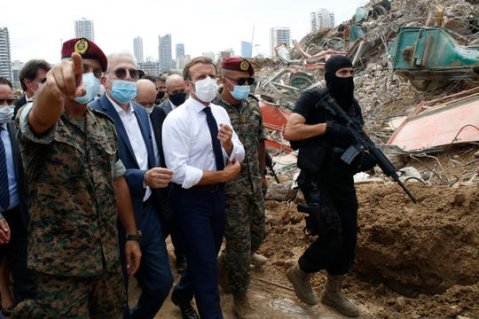 French President Emmanuel Macron, center, visits the devastated site of the explosion at the port of Beirut, Lebanon, Thursday Aug. 6, 2020.