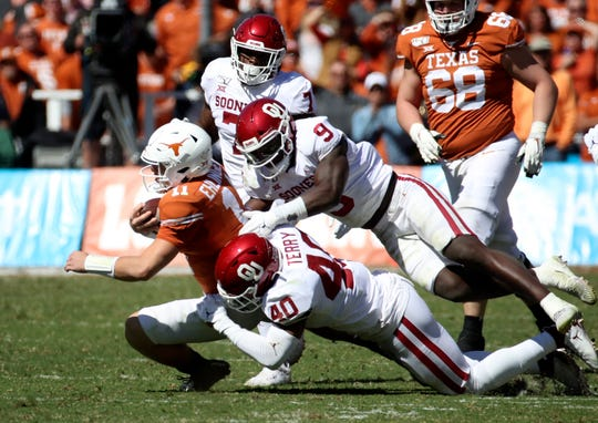Texas quarterback Sam Ehlinger is sacked by Oklahoma's Kenneth Murray and Jon-Michael Terry during the first half of their 2019 game at the Cotton Bowl.