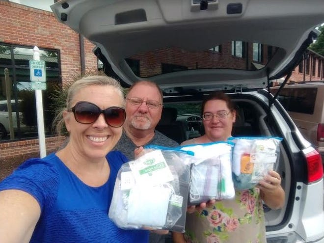 Aundrea Azelton, service chair of Randolph Rotary, gives first-aid bags to Feed Locals First charity. The bags were collected by Randolph Rotary for a service project for July. Feed Locals First directors are Bill Leeper and Sherri Miller.