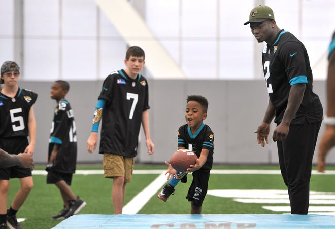 Kaden Moton, 5, pulls in a pass as the Jaguars' Charles Jones (right) looks on as they participate in the Special Olympics Fantasy Camp last year. [Bob Self/Florida Times-Union]