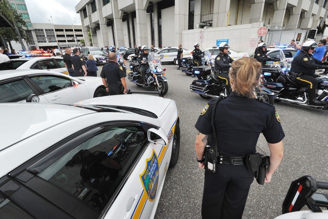 In this May 17, 2018 file photo, Jacksonville police line Edison Avenue as the body of officer Lance Whitaker is escorted to Hardage-Giddens funeral home on Park Street. [Will Dickey/Florida Times-Union]