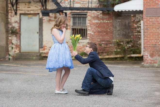 This photo of Caleb Prewitt down on one knee presenting flowers to best friend Brogan Paul  will appear in a video to be streamed Sept. 12 in Times Square in New Yorkas part of the National Down Syndrome Society's annual video presentation in the celebrated destination. [Logan Rose]