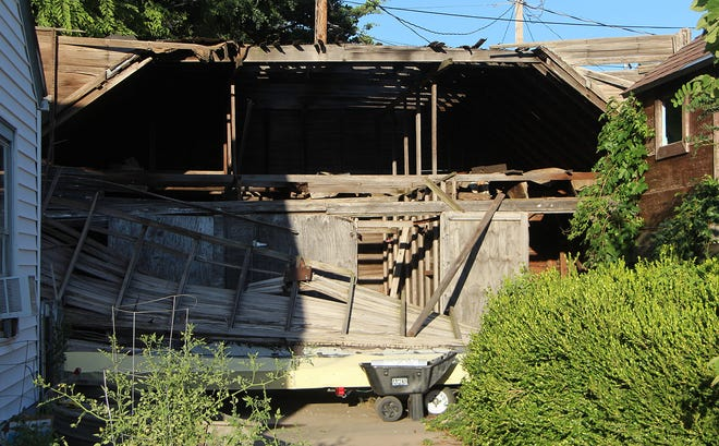 The front of a garage lies on the ground after it collapsed at 216 South Hamilton on July 31. No one was injured in the collapse.