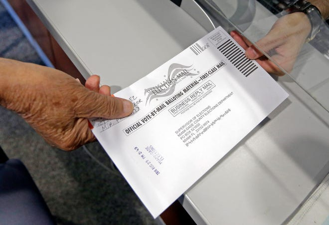 A voter hands his absentee ballot to a Miami-Dade County elections official in 2016.