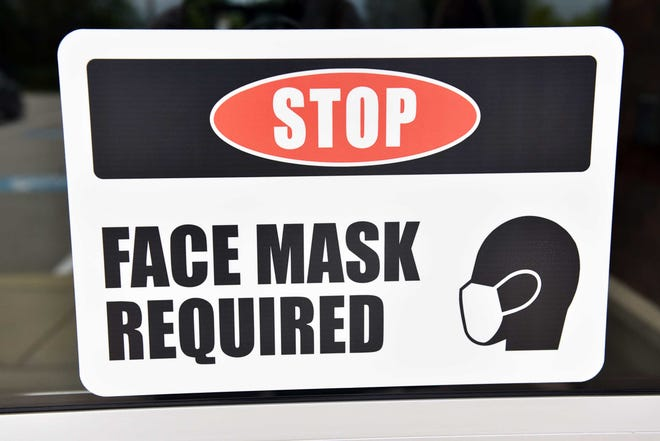A sign on the front door of SandHoke Early College High School in Hoke County says face masks are required for entry into the school.