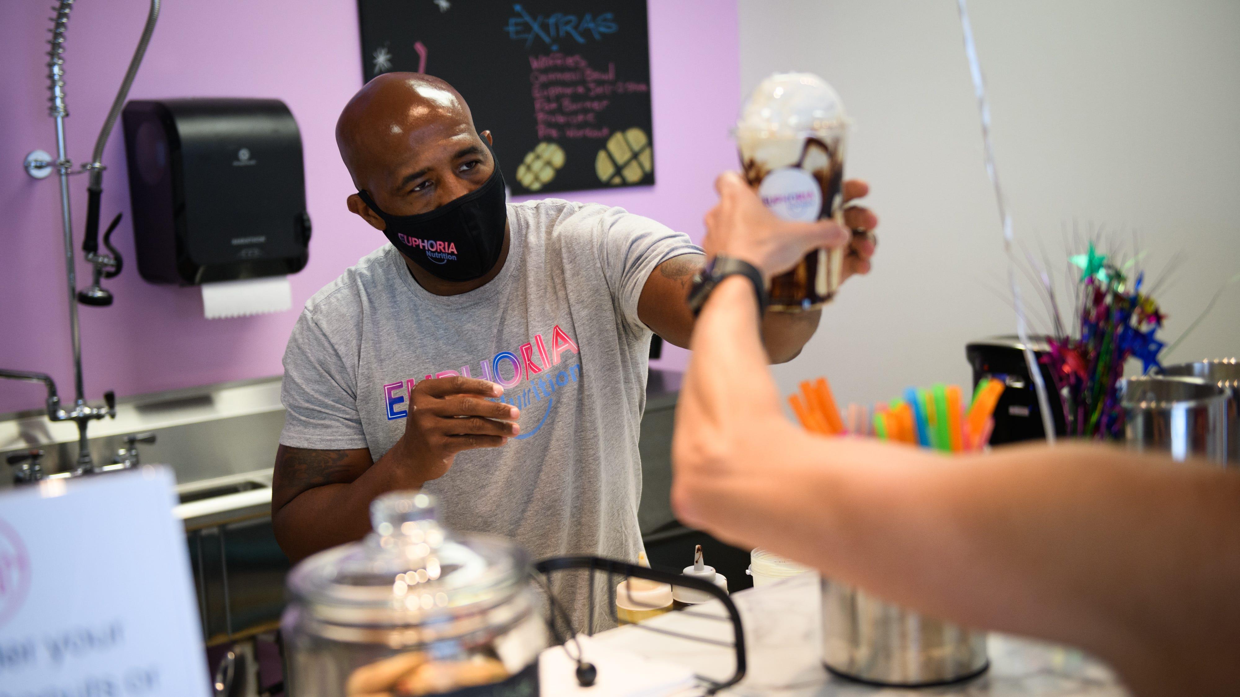 Everitt Willamson hands a shake to a customer at Euphoria Nutrition on Friday, Aug. 7, 2020.