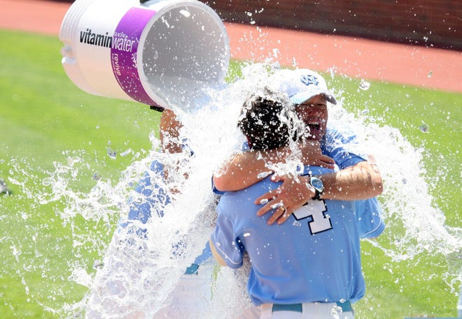 Mike Fox embraces former player Garrett Gore in celebration of a North Carolina baseball victory.