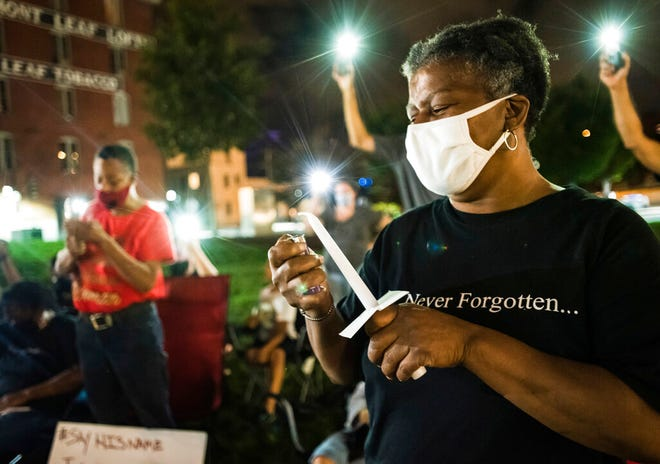 Janice Jordan, one of John Neville's aunts, lights a candle during a vigil for Neville on Wednesday, Aug. 5, 2020, in Bailey Park in Winston-Salem, N.C. Demonstrators held the vigil to demand justice for Neville, a Black man who died days after his December 2019 arrest following the release of body camera videos that showed him struggling with guards and yelling he couldn't breathe as they restrained him.   (Allison Lee Isley/The Winston-Salem Journal via AP)