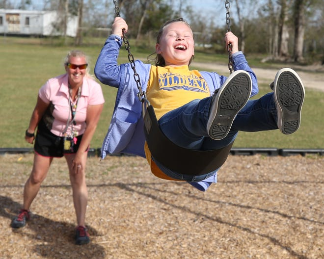 Davina Lucas gives second grade student Arianna Hanstra a push on the swing on March 8, 2019 at Waller Elementary.