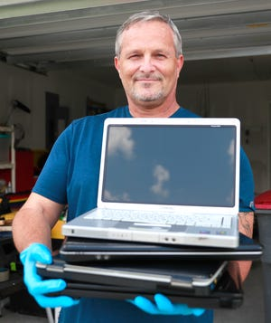 Paul Jones holds a stack of repaired laptops at his home on Aug. 7, 2020. Jones is raising funds to rebuild laptops to give to students.  [PATTI BLAKE/THE NEWS HERALD]