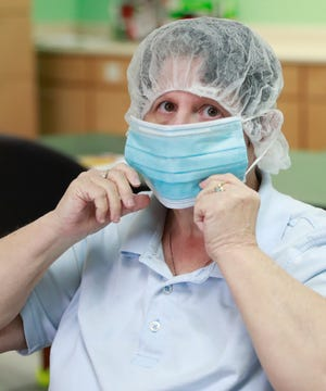 Becky G. pulls on a disposable face mask before sorting flatware on Aug. 7, 2020 at The Arc of the Bay. Unifirst donated 2,000 face masks to the nonprofit organization that helps disabled adults learn new skills. [PATTI BLAKE/THE NEWS HERALD]