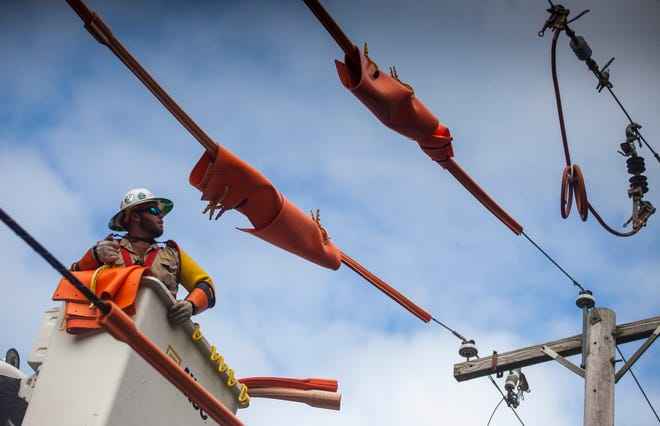 Out-of-state contractors work repairing downed power lines on Ridge Avenue in Lakewood on Aug. 7, 2020. Jersey Central Power and Light brought in crews to help restore power to the hundreds of thousands of customers affected by Tropical Storm Isaías.