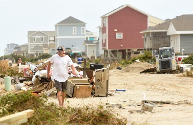 A man walks among the hurricane debris on West Beach Drive on Oak Island on Thursday Aug. 6, 2020, following Hurricane Isaias. [KEN BLEVINS/STARNEWS]