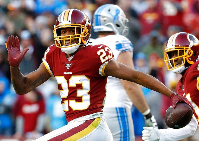 FILE - In this Nov. 24, 2019, file photo, then Washington Redskins cornerback Quinton Dunbar (23) reacts after intercepting a pass during the second half of an NFL football game in Landover, Md. Seattle Seahawks cornerback Quinton Dunbar, New York Giants cornerback DeAndre Baker and Washington receiver Cody Latimer have been put on the NFL's Commissioner Exempt List while facing felony charges from offseason incidents. Baker and Dunbar were charged with armed robbery at a cookout in Florida in May 2020.  (AP Photo/Patrick Semansky, File)