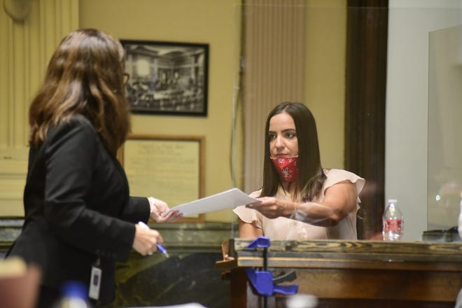 Megan Futchi, right, hands a piece of evidence back to Maggie Tomaro, a state senior assistant attorney general-special prosecutor who is prosecuting the Jason Tupps case, Thursday in the Crawford County Courthouse.